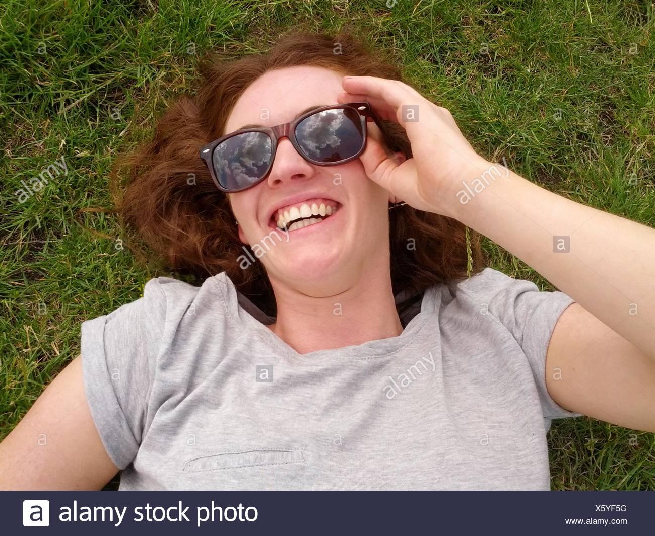 Mujer sonriente tumbado sobre el césped Imagen De Stock