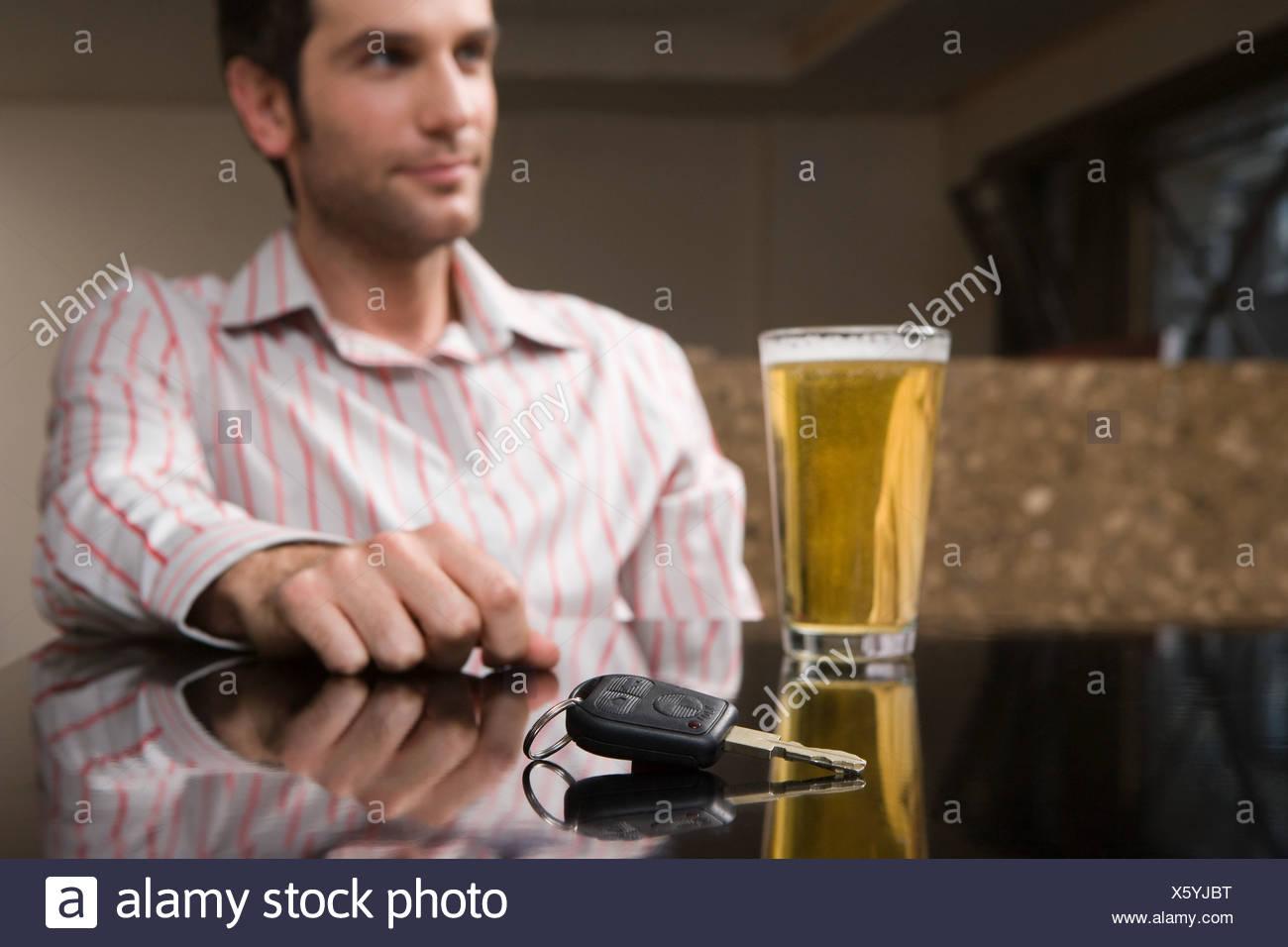 Las llaves del coche y una pinta de cerveza Foto de stock