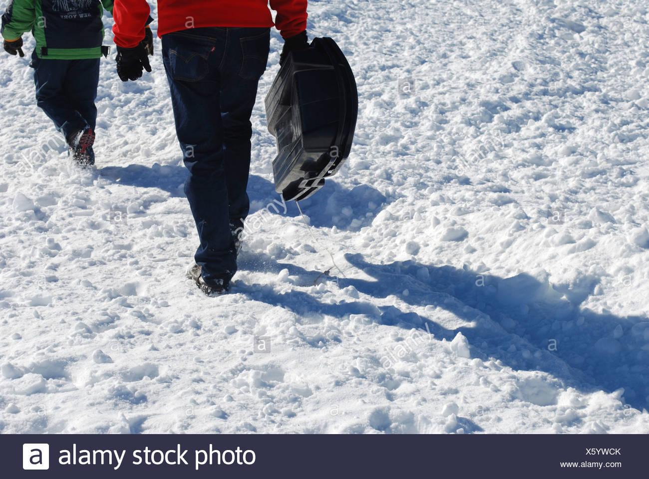 Niño de 7 lleva su trineo back up la ladera de montaña cubiertas de nieve Foto de stock
