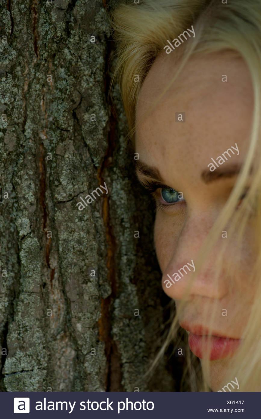 Mujer joven RECOSTADA contra el tronco del árbol, mirando tristemente lejos Imagen De Stock