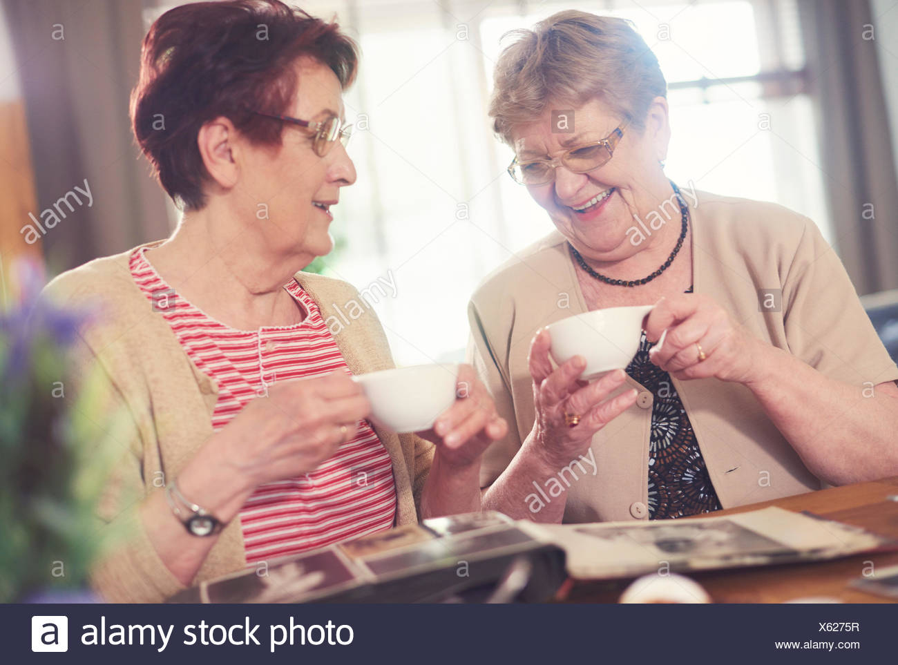 Dos mujeres mayores riendo mientras mira el álbum de fotos sobre la mesa Foto de stock