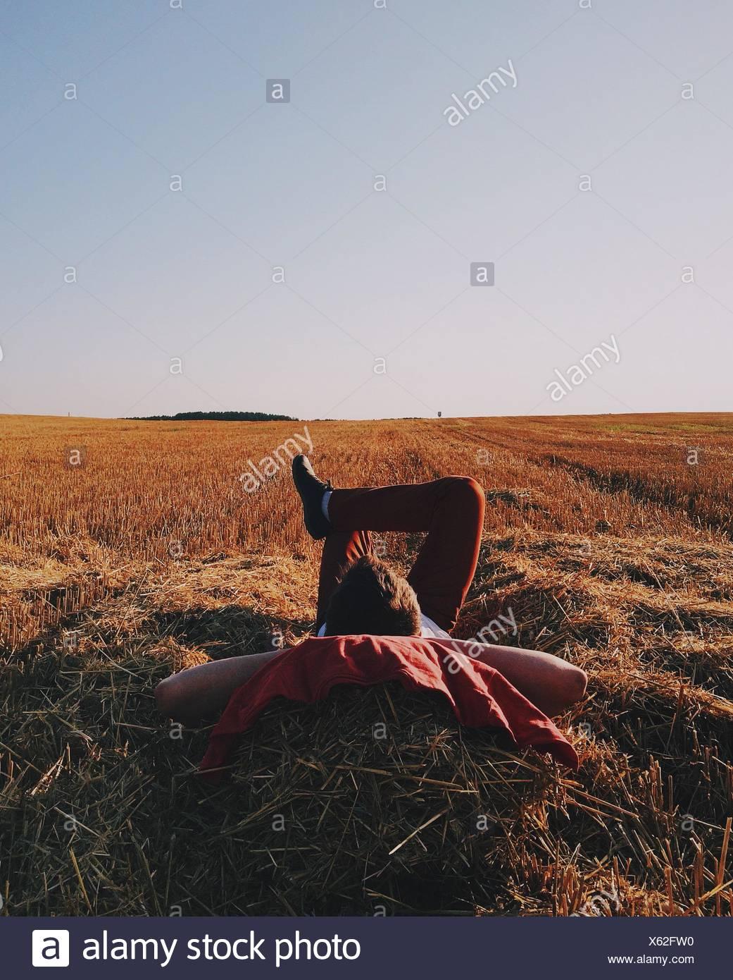 El hombre acostado sobre la paja en el campo Imagen De Stock