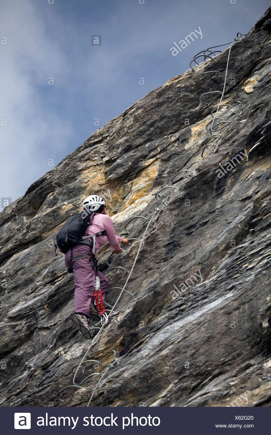 Una joven mujer subiendo una escalera incrustada en la roca mientras practica el deporte de Vía ferrata en los Alpes franceses. Imagen De Stock