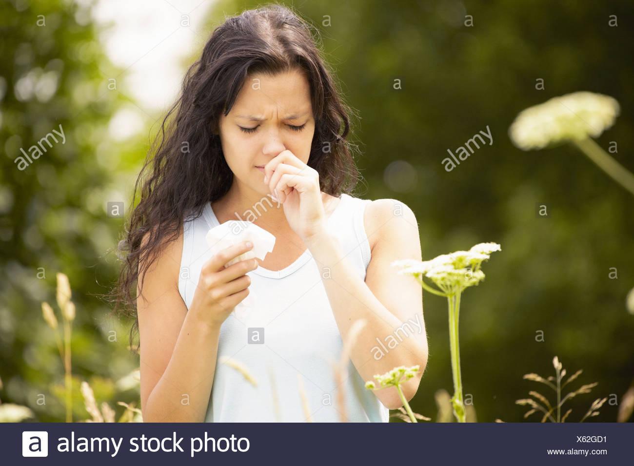 Chica con tejido frotando la nariz Imagen De Stock