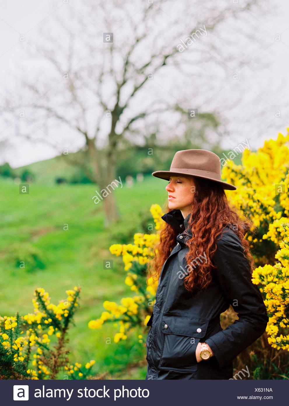 Una mujer con largo cabello rizado con sombrero, por un florecimiento tojo bush. Imagen De Stock