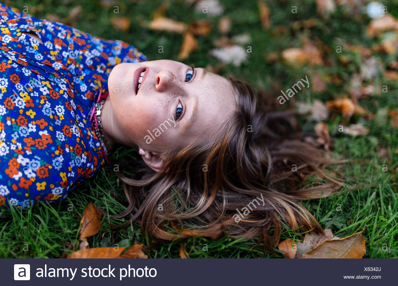 Retrato de niña acostada sobre una pradera Imagen De Stock
