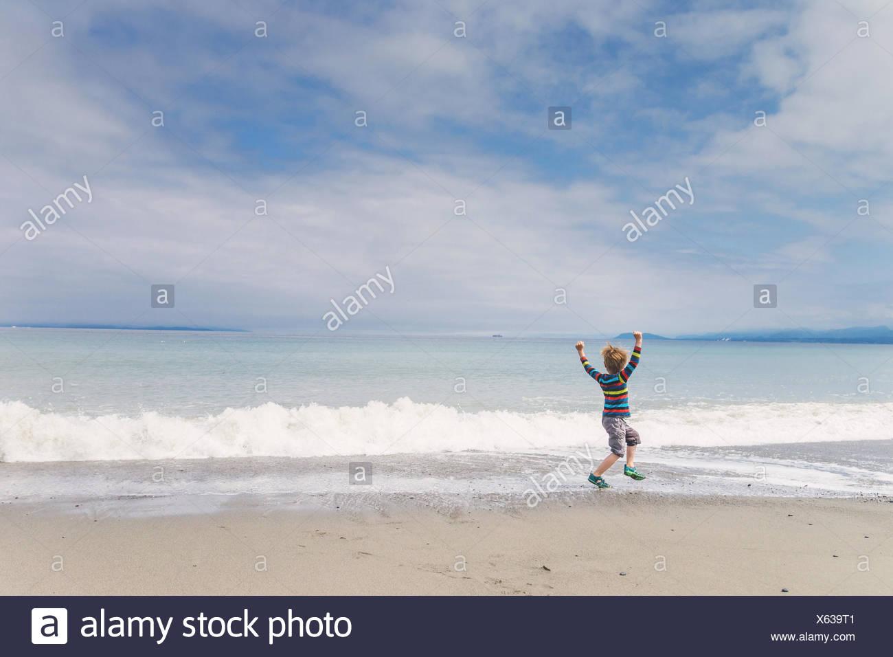Boy saltar de alegría en la playa Imagen De Stock