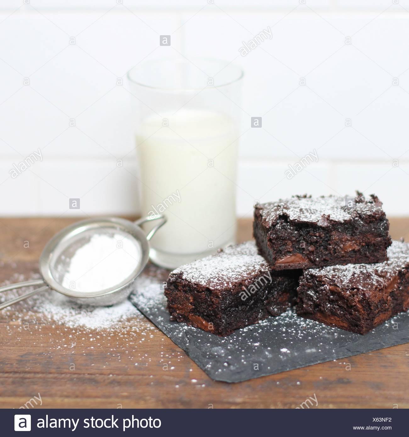 Brownies de chocolate espolvoreado con azúcar glas y vaso de leche Imagen De Stock