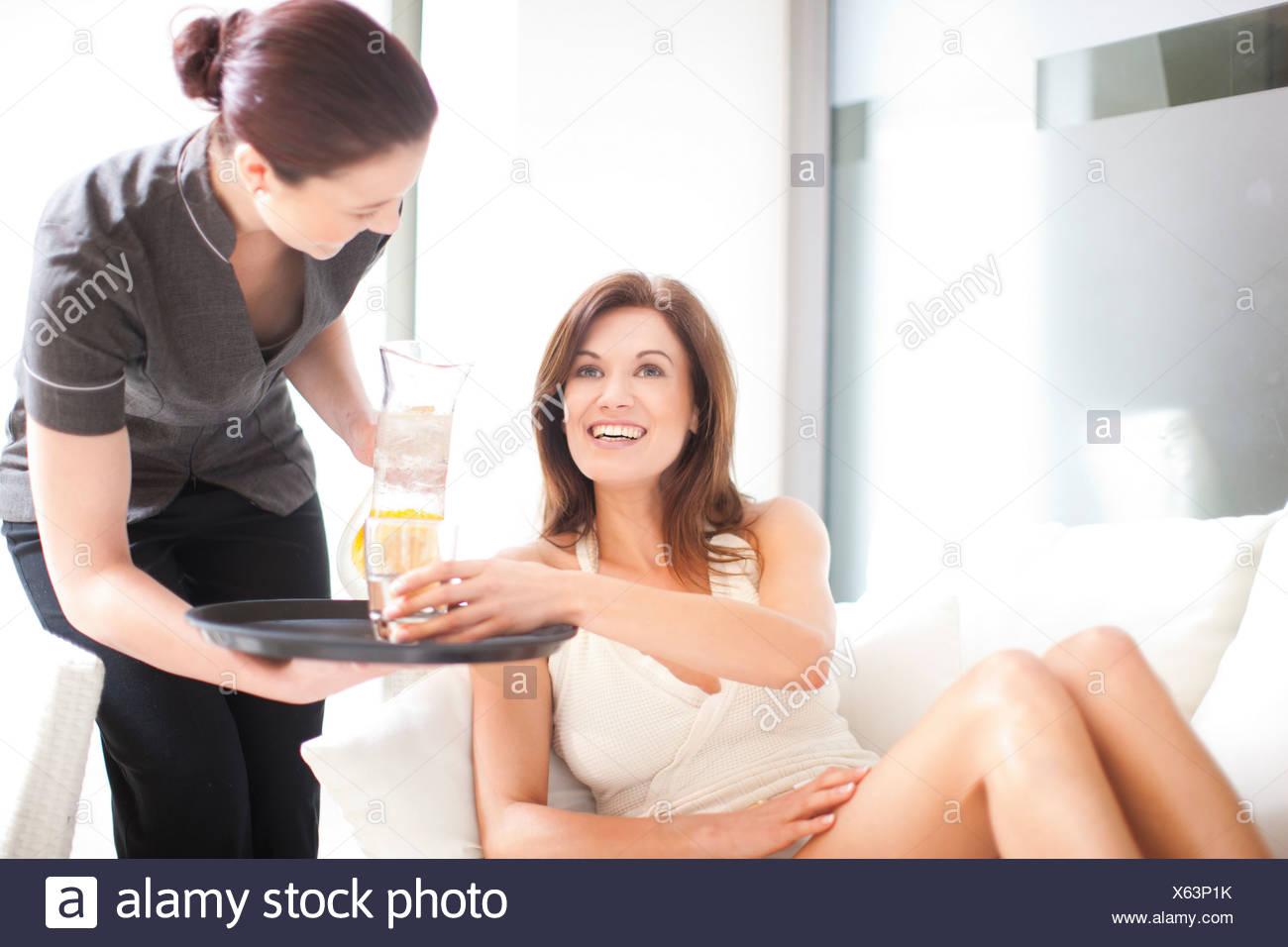 Trabajador de servicio vertiendo refresco para mujer piscina. Imagen De Stock