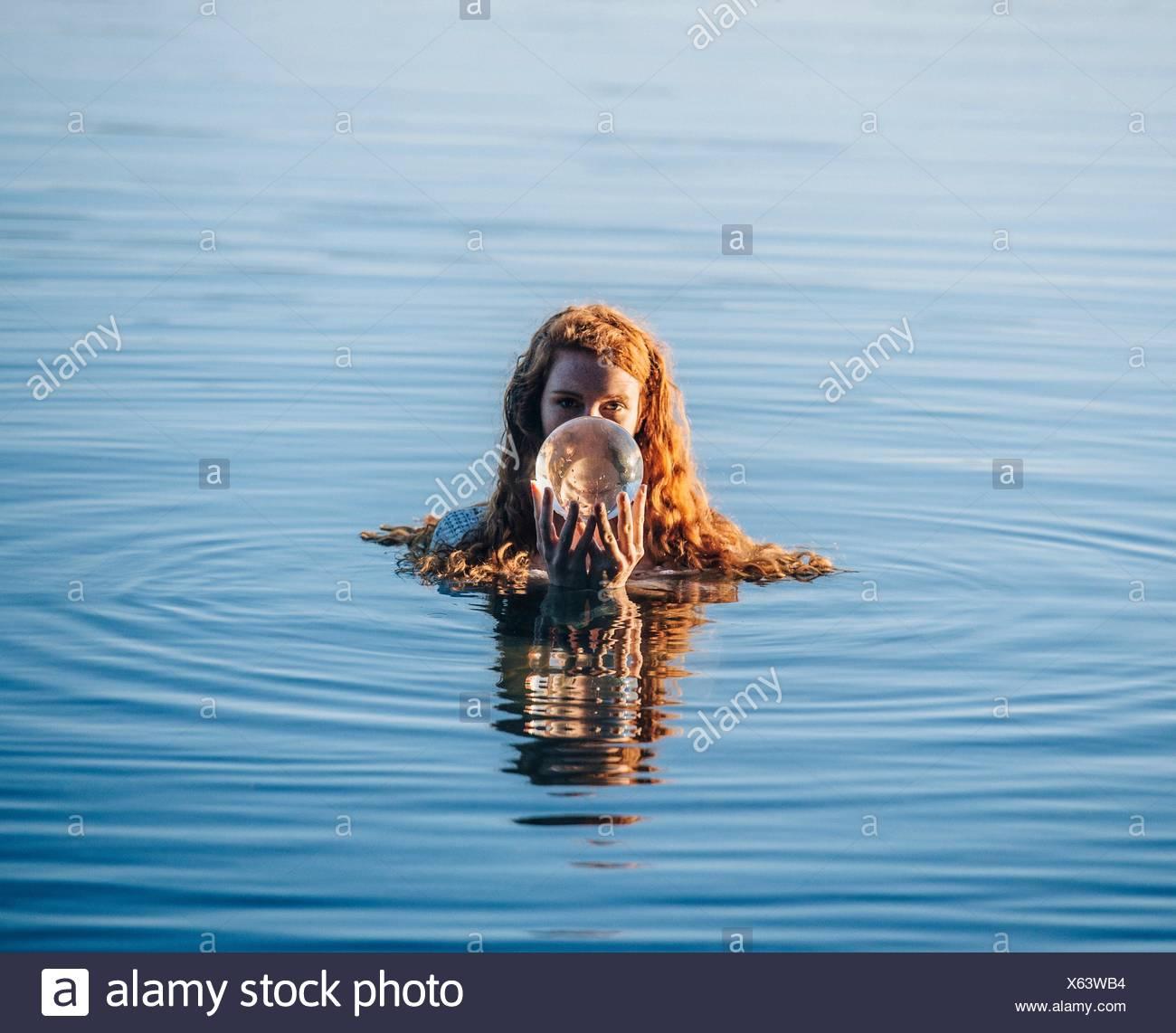 Cabeza y hombros de la mujer joven con largo pelo rojo en el lago sosteniendo la bola de cristal Foto de stock