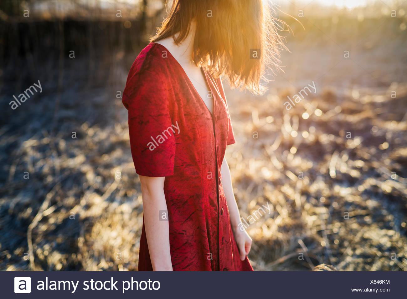 Finlandia, Varsinais-Suomi, joven mujer de pelo rojo en el vestido rojo de pie en la luz del sol Imagen De Stock