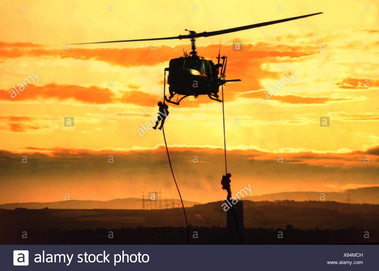 Un helicóptero militar. Helicópteros de combate, silueta, soldado, cuerda, los militares, la fuerza de tarea, luchar contra la entrada, prácticas militares, la operación militar, en la práctica, HELICÓPTERO, HELICÓPTERO, aclaración helicóptero, el helicóptero de ataque, Filtro espectral amarillo Imagen De Stock