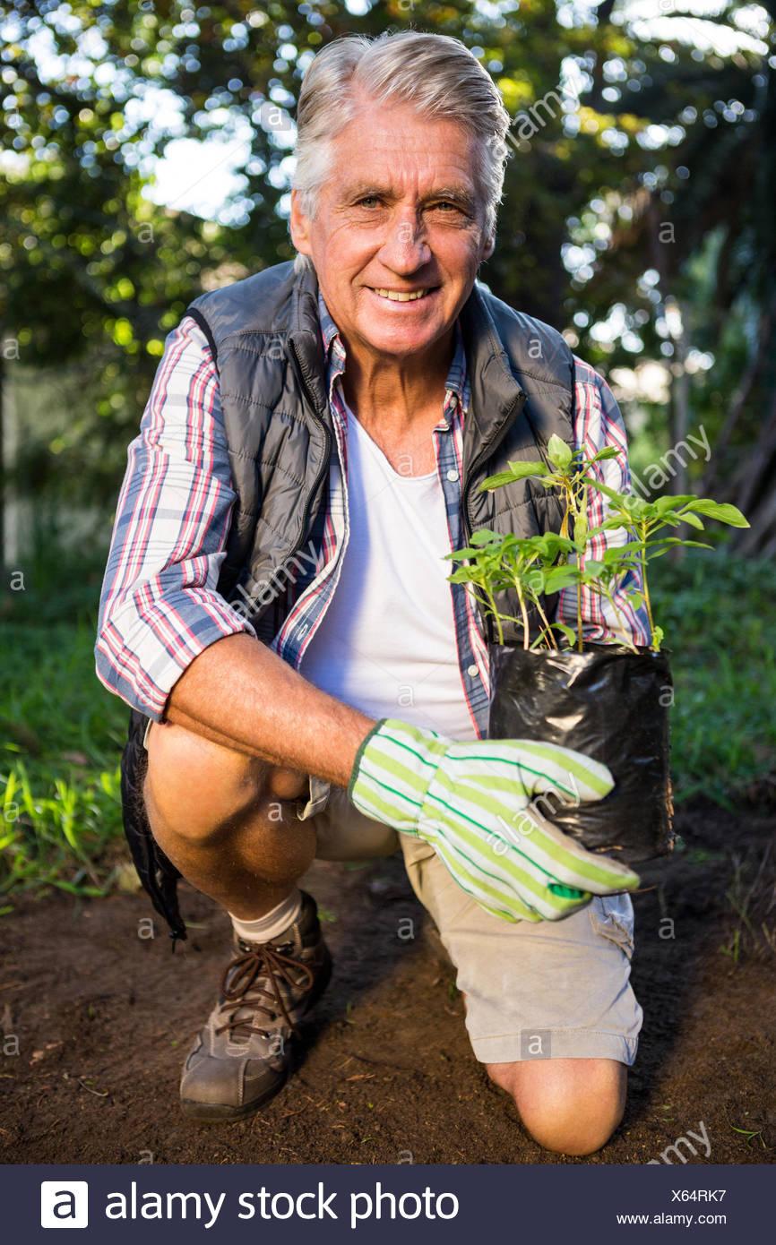 Retrato de feliz jardinero arrodillado con planta en maceta en el jardín Imagen De Stock