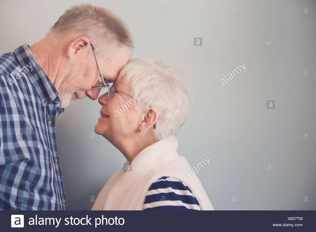 Las parejas ancianas tocar frentes y sonriente Imagen De Stock