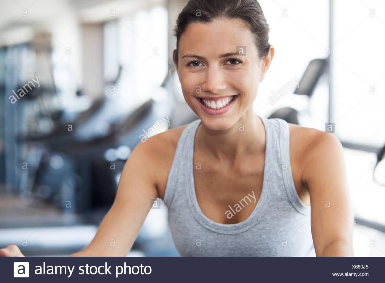 Mujer joven con máquina de ejercicio en el gimnasio Imagen De Stock