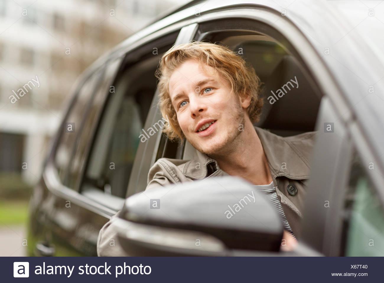 Retrato del joven sonriente de asomarse a la ventana de coche viendo algo Imagen De Stock
