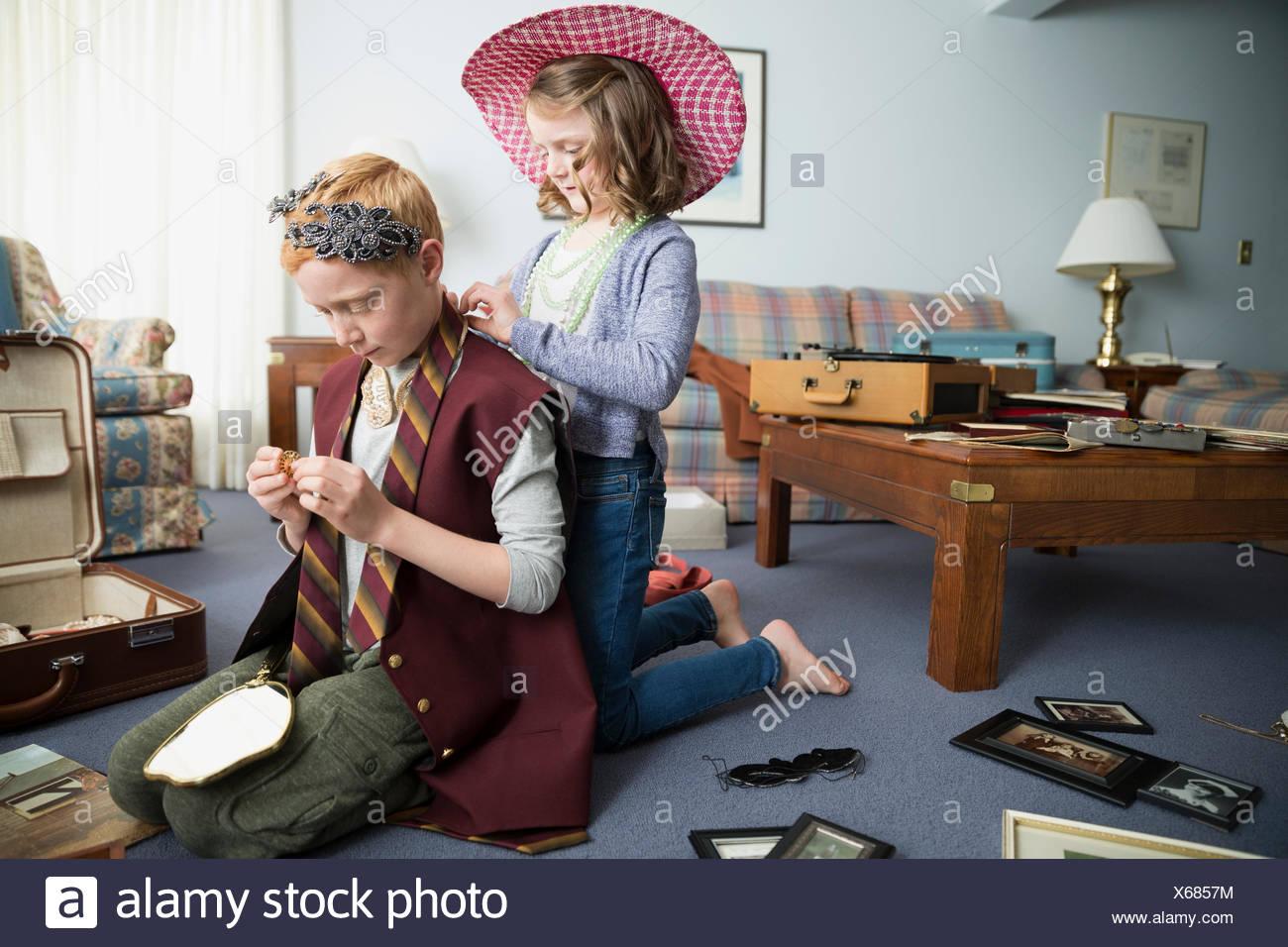 Hermano y hermana, tratando de ropa antigua Imagen De Stock