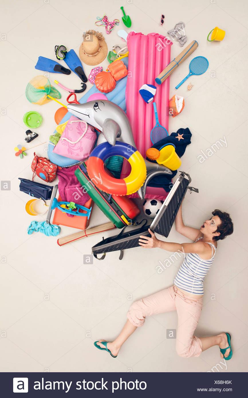 Alemania, escena artificial con la mujer abriendo el equipaje lleno de juguetes de playa Foto de stock