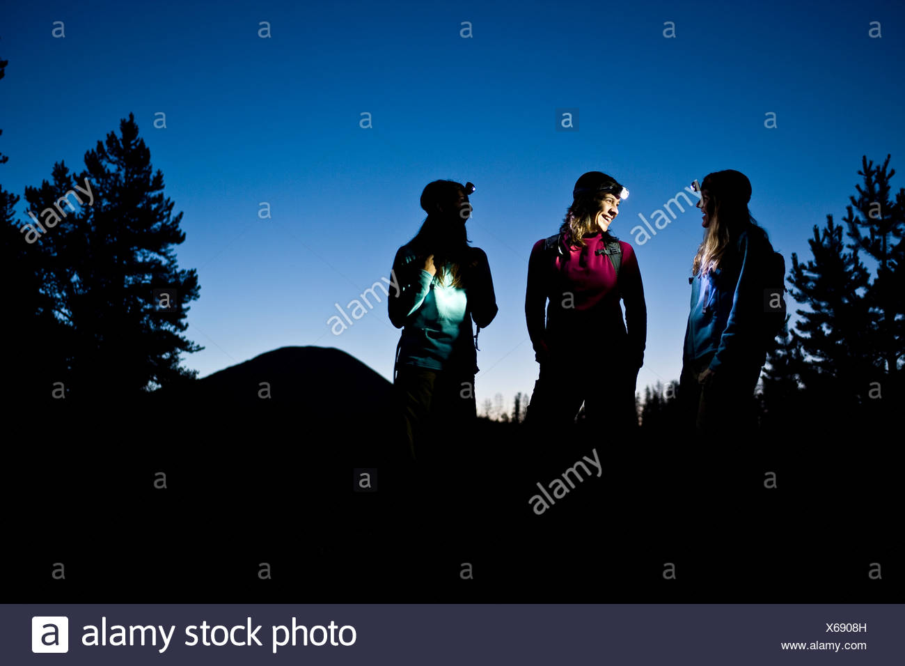 Tres mujeres hablan mientras disfruta de una caminata al atardecer iluminado por el faro. Foto de stock