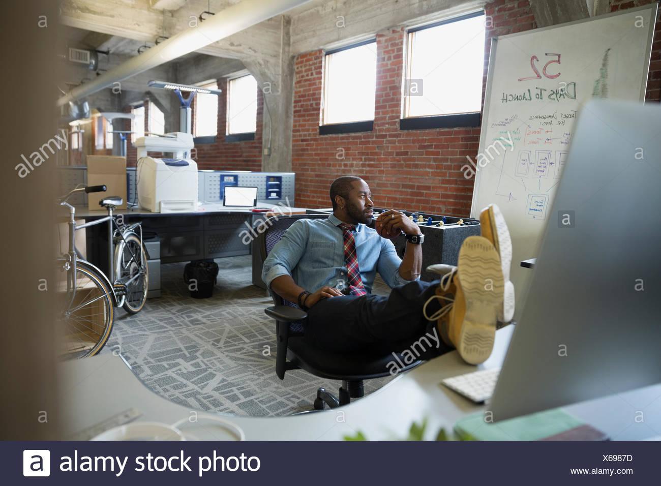 Empresario con los pies para arriba en la nueva oficina de escritorio Foto de stock