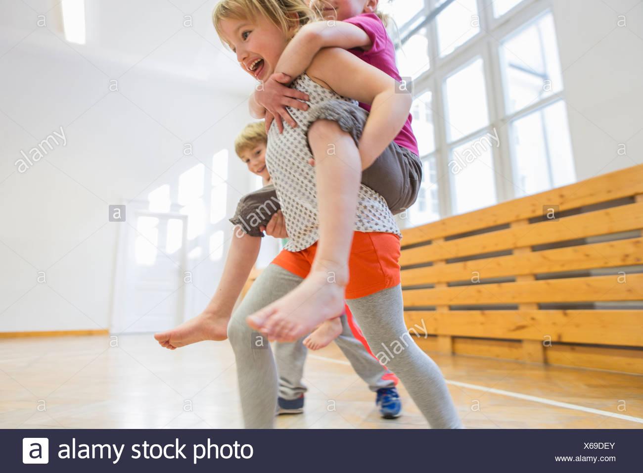 Los niños que piggy back carrera en sala escolar Foto de stock