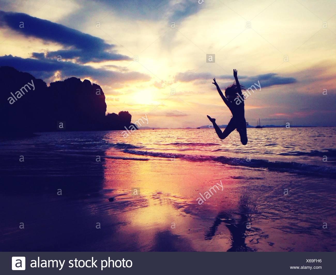 Silueta Mujer disfrutando en la playa contra el cielo al atardecer Imagen De Stock