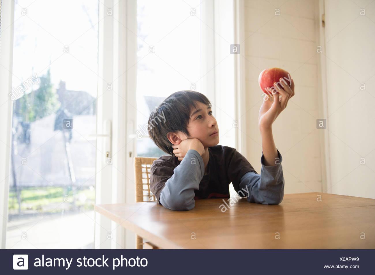 Muchacho sentado a la mesa, sosteniendo una manzana en frente de él Imagen De Stock