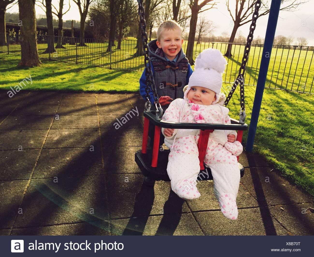 Lindo hermano Niño empujando a su hermana en Swing en Playground Imagen De Stock