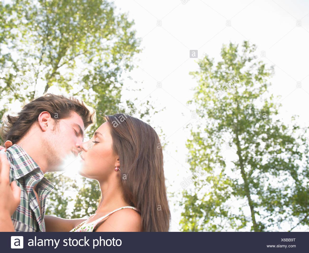 Pareja besándose bajo los árboles Imagen De Stock