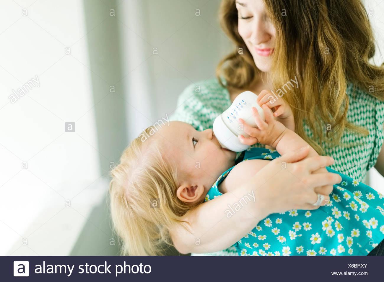 Madre alimentando Baby Girl (12-17 meses) en la sala de estar Imagen De Stock