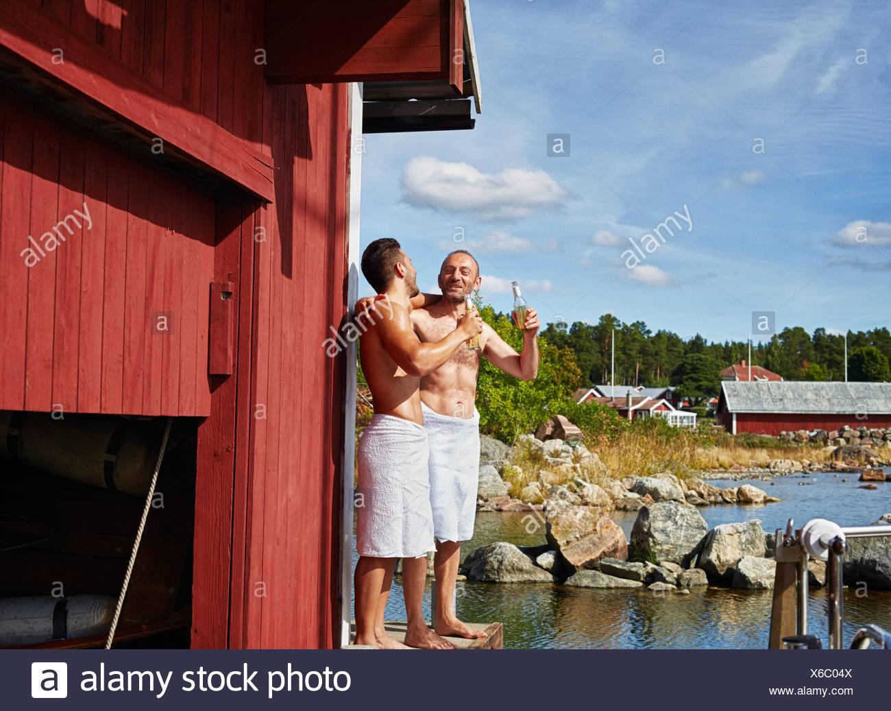 Dos hombres con cervezas fuera sauna Foto de stock