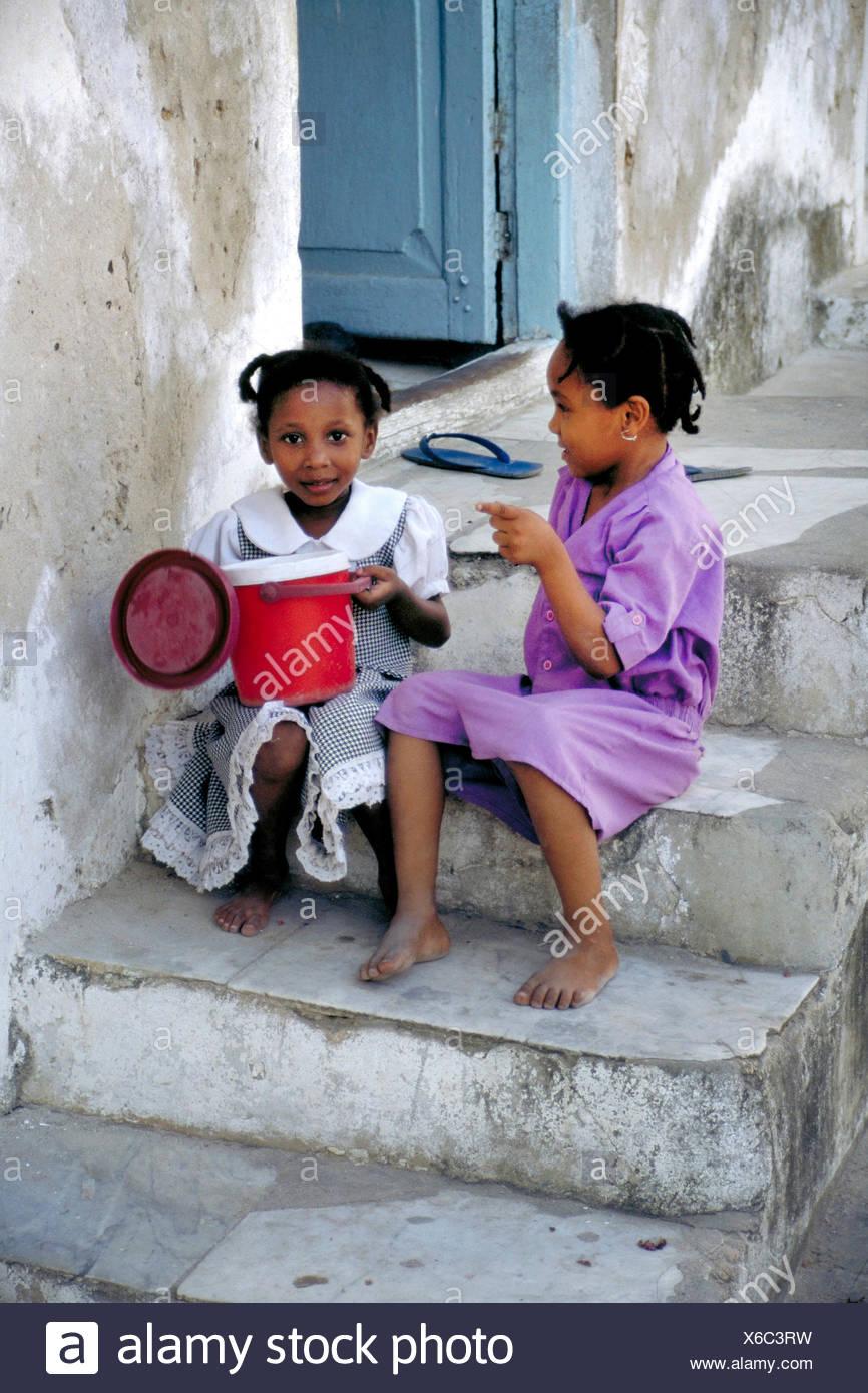Dos pequeñas muchachas africanas sentados juntos en una escalera exterior y chatear, Tanzania Imagen De Stock