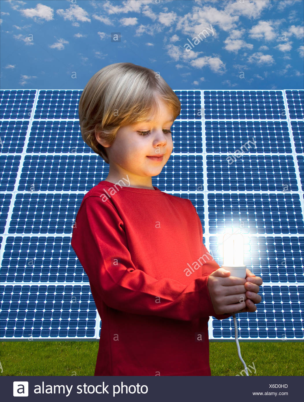 Chico con bombilla por paneles solares Imagen De Stock