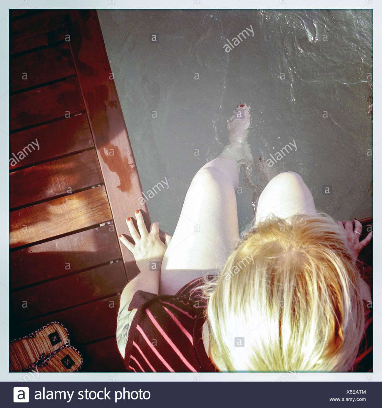 Un alto ángulo de visualización de la mujer sentada en el borde de la piscina Imagen De Stock