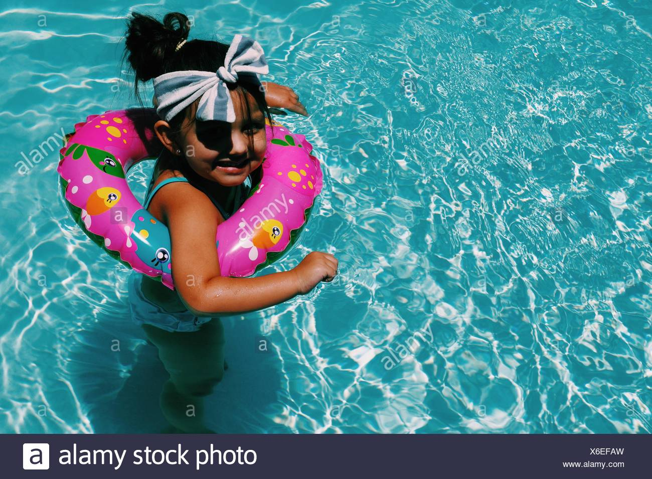 Un alto ángulo de vista de niña alegre nadar en piscina con salvavidas Foto de stock