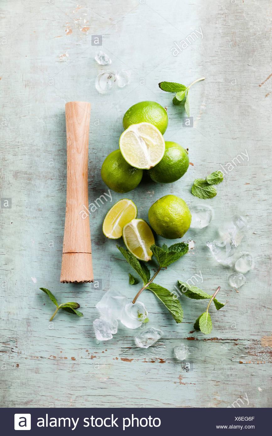 Ingredientes para hacer mojitos, cubitos de hielo, hojas de menta y limón, sobre fondo azul. Imagen De Stock