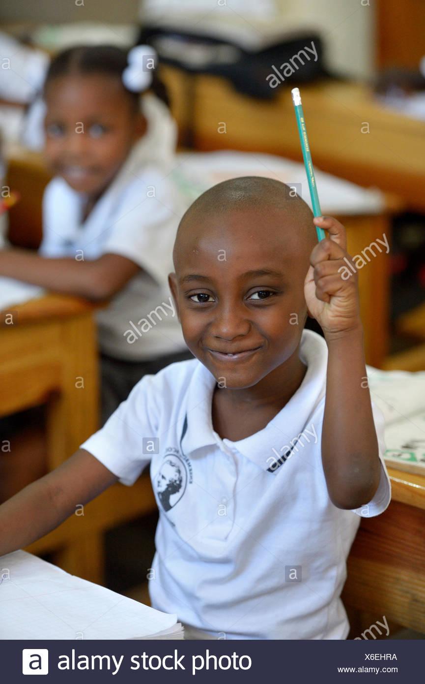 El colegial levantando su mano en clase, la clase de la Escuela Primaria Basile Moreau, Carrefour, Port-au-Prince, el Departamento Ouest Imagen De Stock