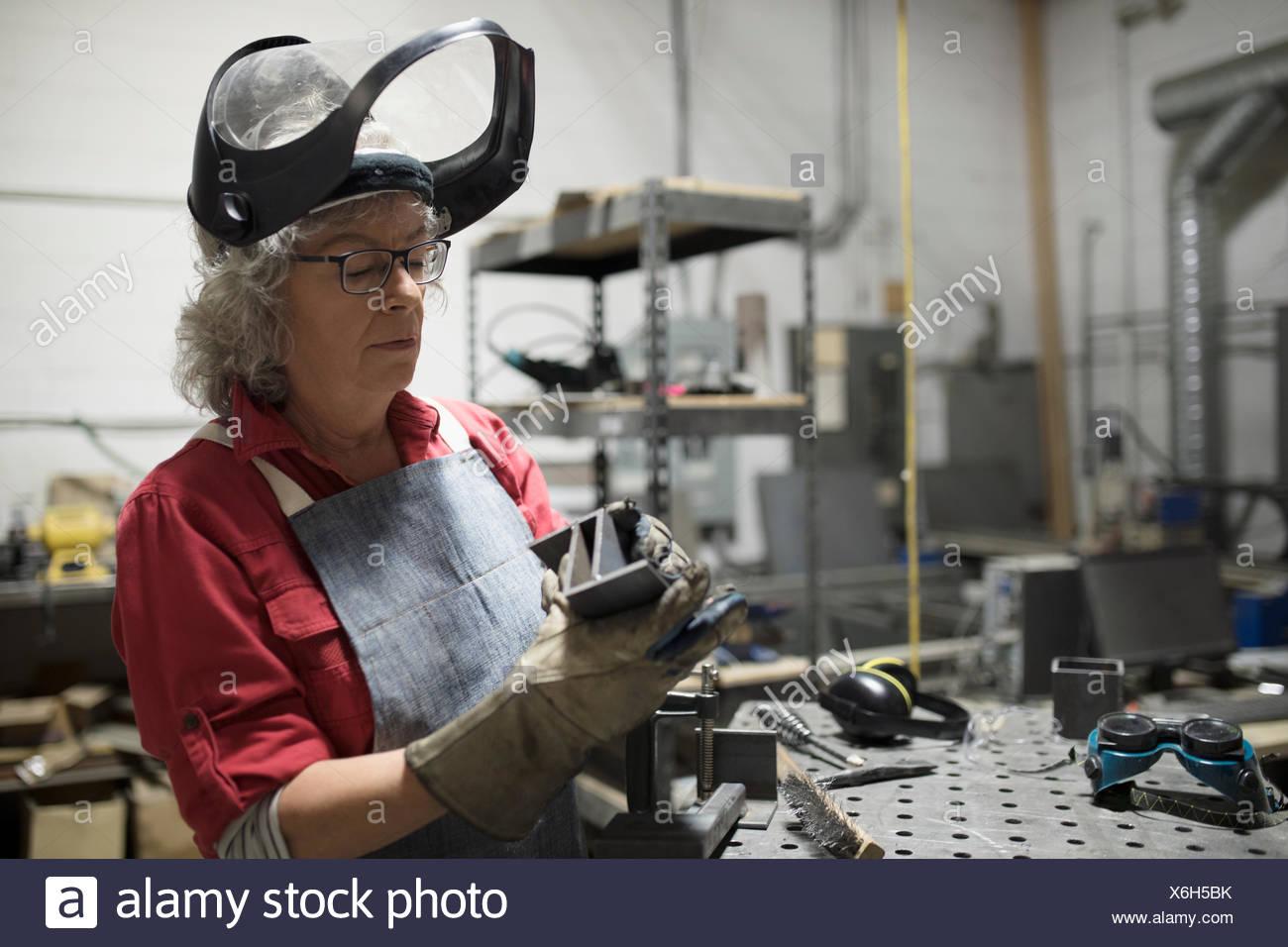 Soldador femenino senior examinar parte de acero en el taller Imagen De Stock
