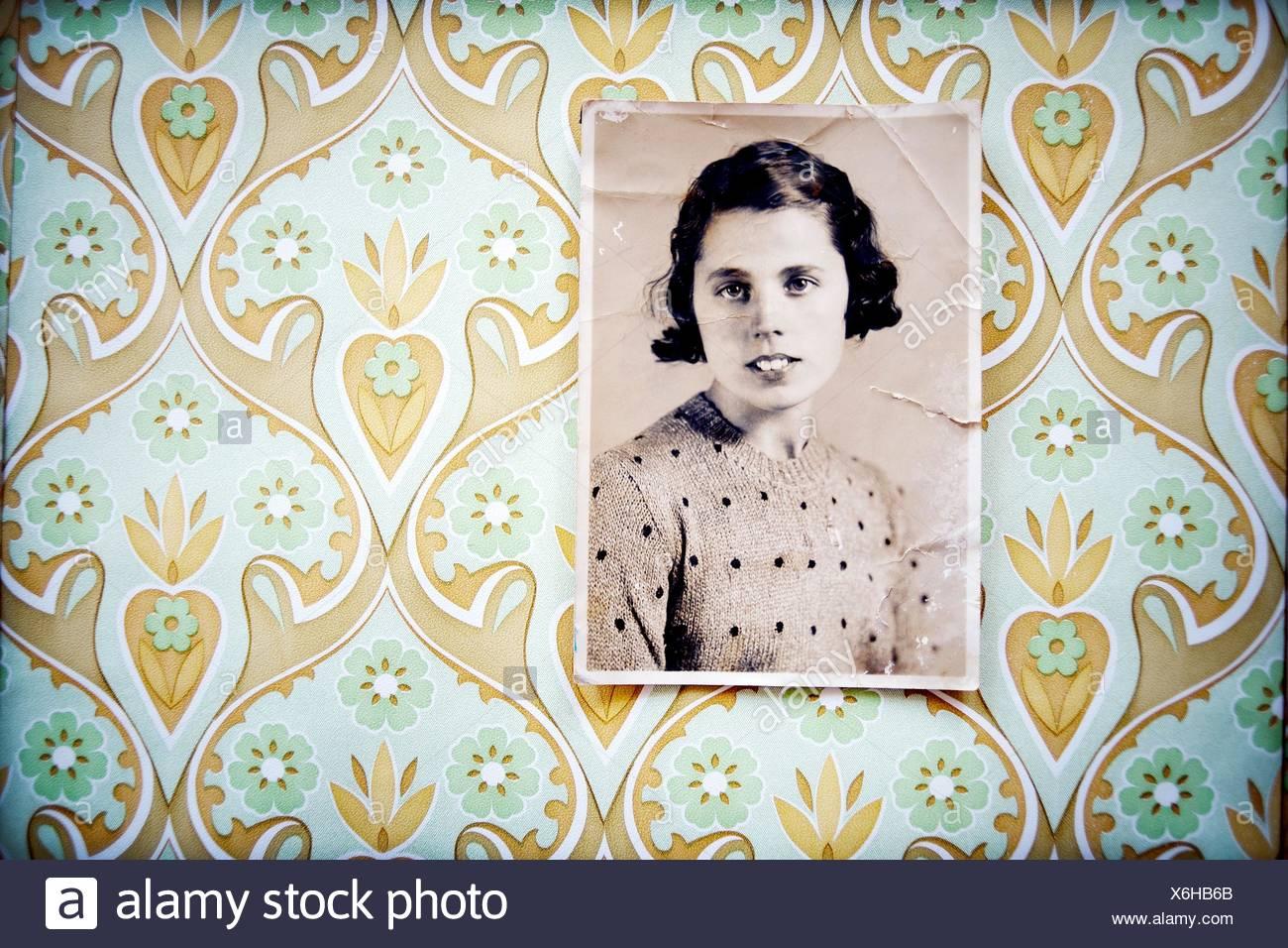 Retrato en blanco y negro de mujer de los años 40 colgada en la pared con papel pintado, vintage, retrato en blanco y negro de un Imagen De Stock
