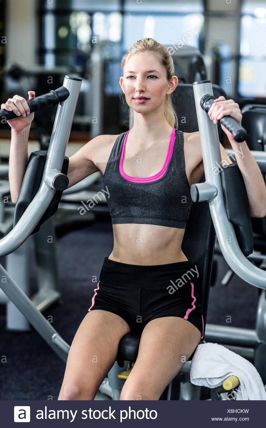 Colocar mujer mediante máquina de ejercicio Imagen De Stock