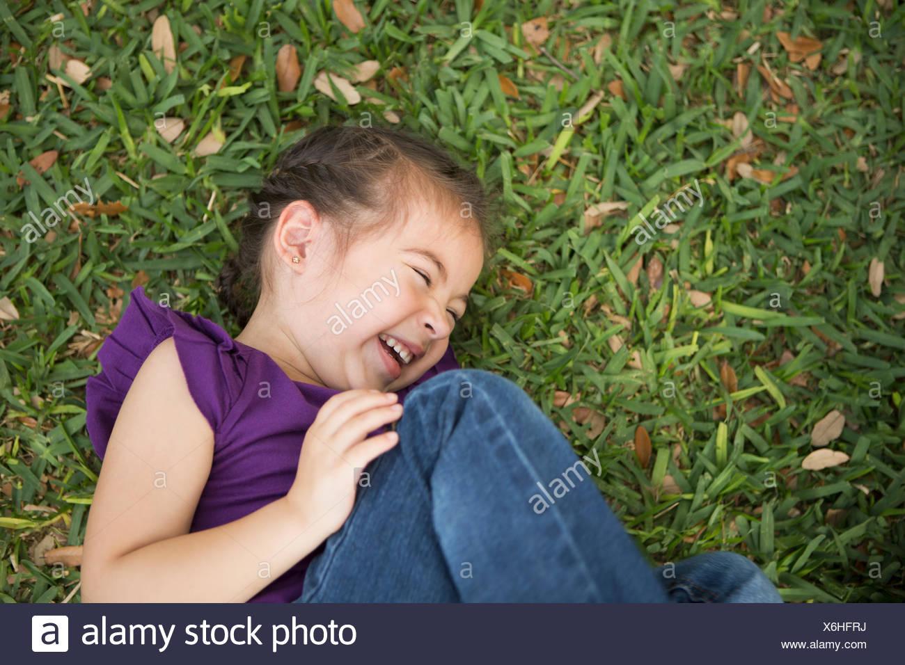 Una chica acostada de lado con sus rodillas flexionadas riendo. Imagen De Stock