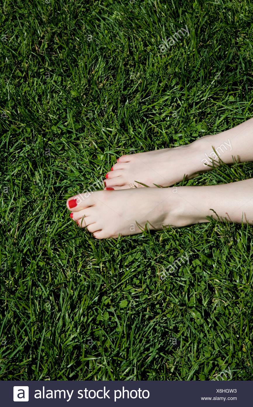 Una joven mujer pies descalzos con uñas pintadas de rojo tumbado ...
