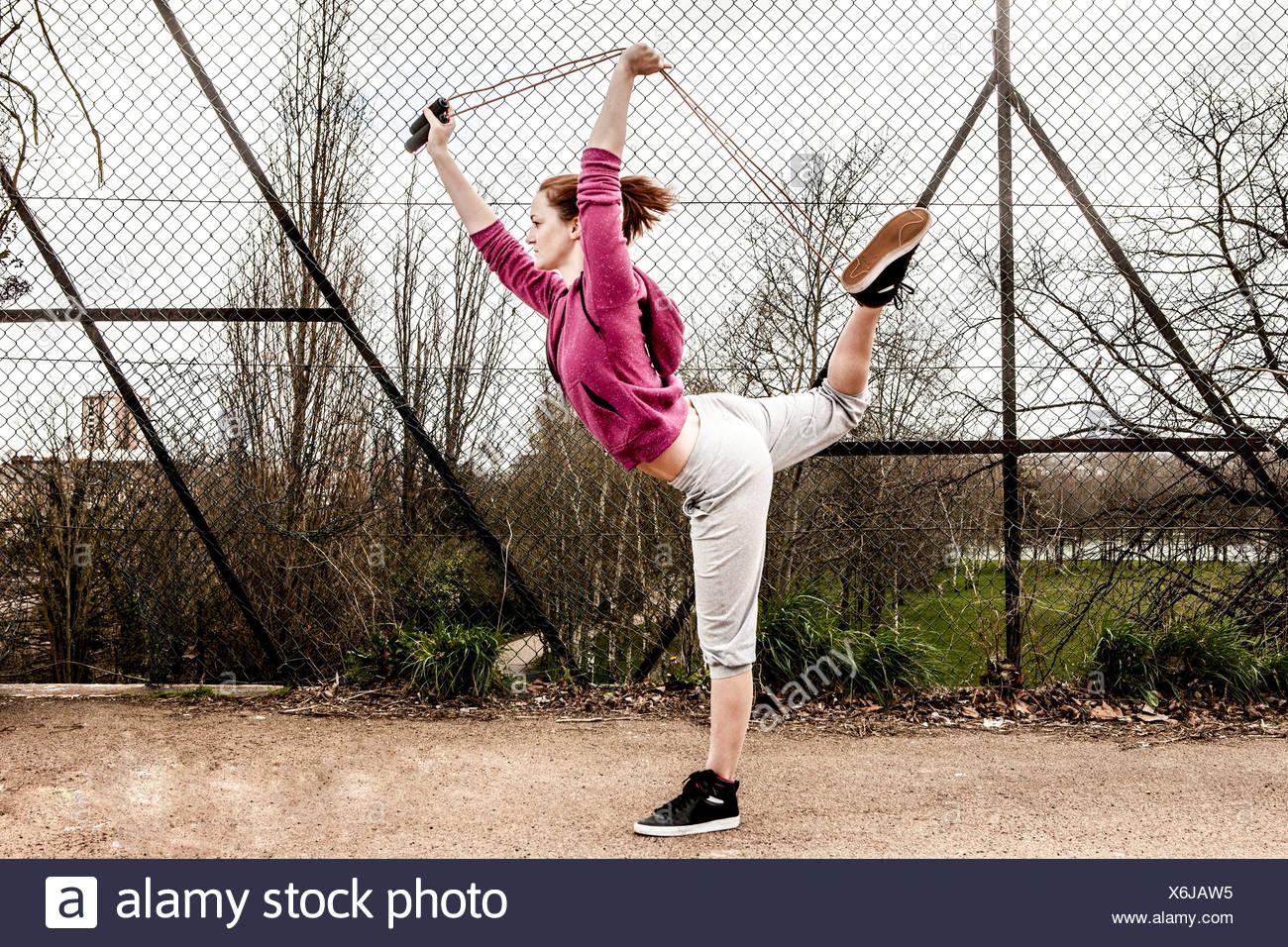 Mujer en el hoodie tirando de la cuerda de pilates desde detrás de la pierna doblada Imagen De Stock