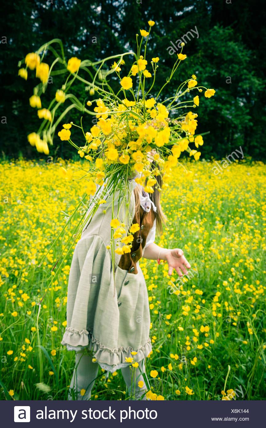 Vestidos de niña vestidos al estilo country arrojando ranúnculos, Ranunculus, en el aire Imagen De Stock