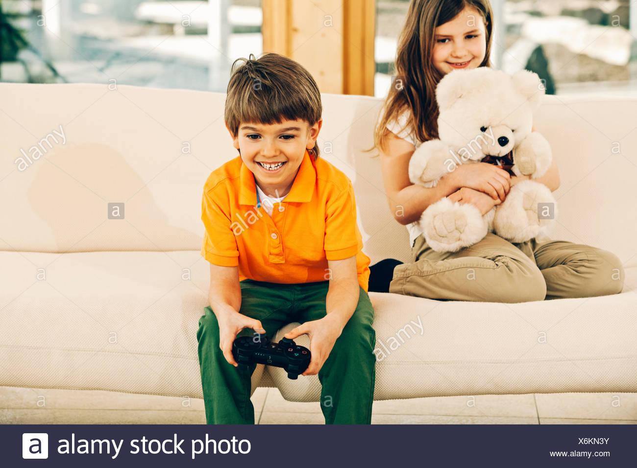 Niño jugando juego de vídeo en sala hermana celebración osito Imagen De Stock