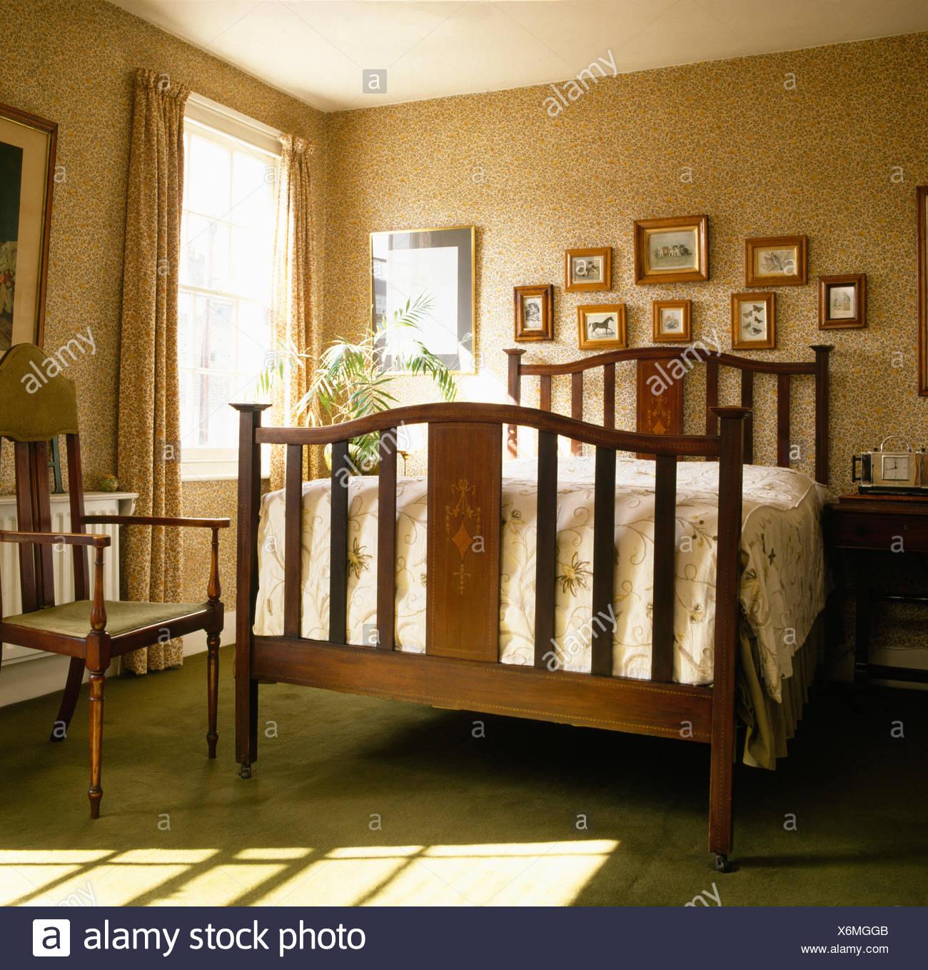 Empapelado de llanura y cama de madera en dormitorio de estilo 1940 Foto de stock