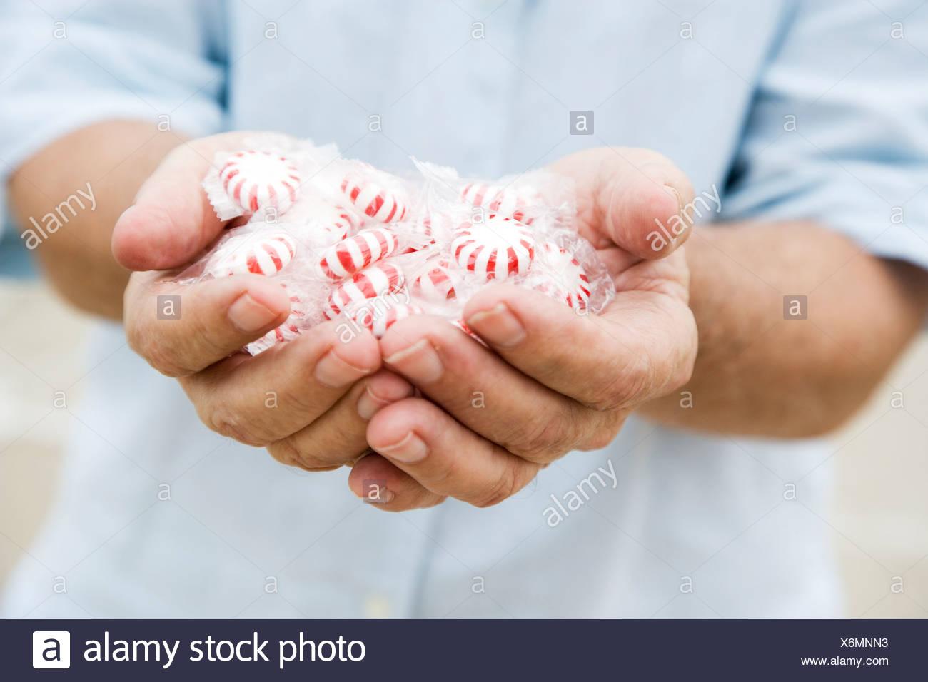 La mano que sostiene el hombre Senior dulces o golosinas Imagen De Stock