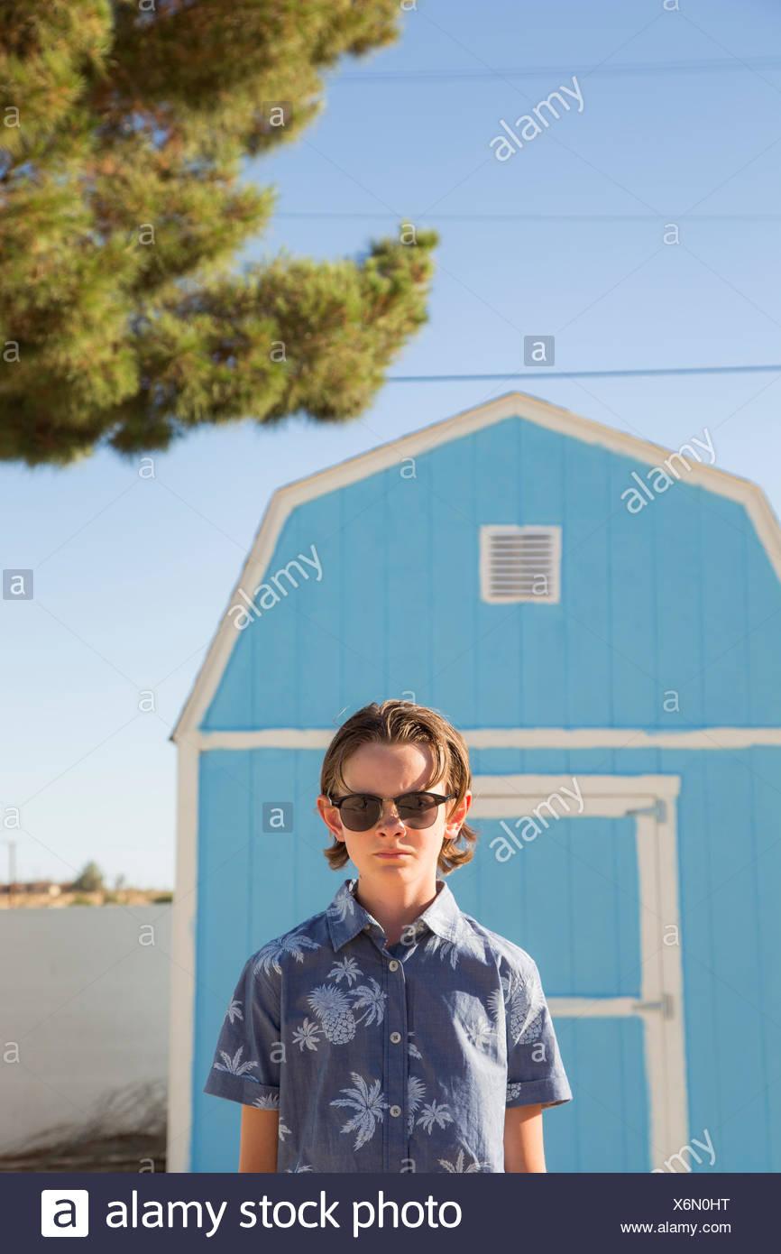 California, Estados Unidos, boy (14-15) con gafas de sol de pie en frente del granero azul Imagen De Stock