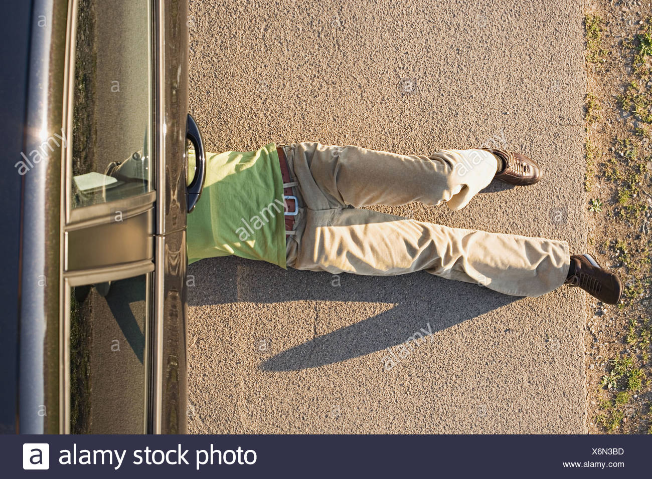 Hombre bajo un auto Foto de stock