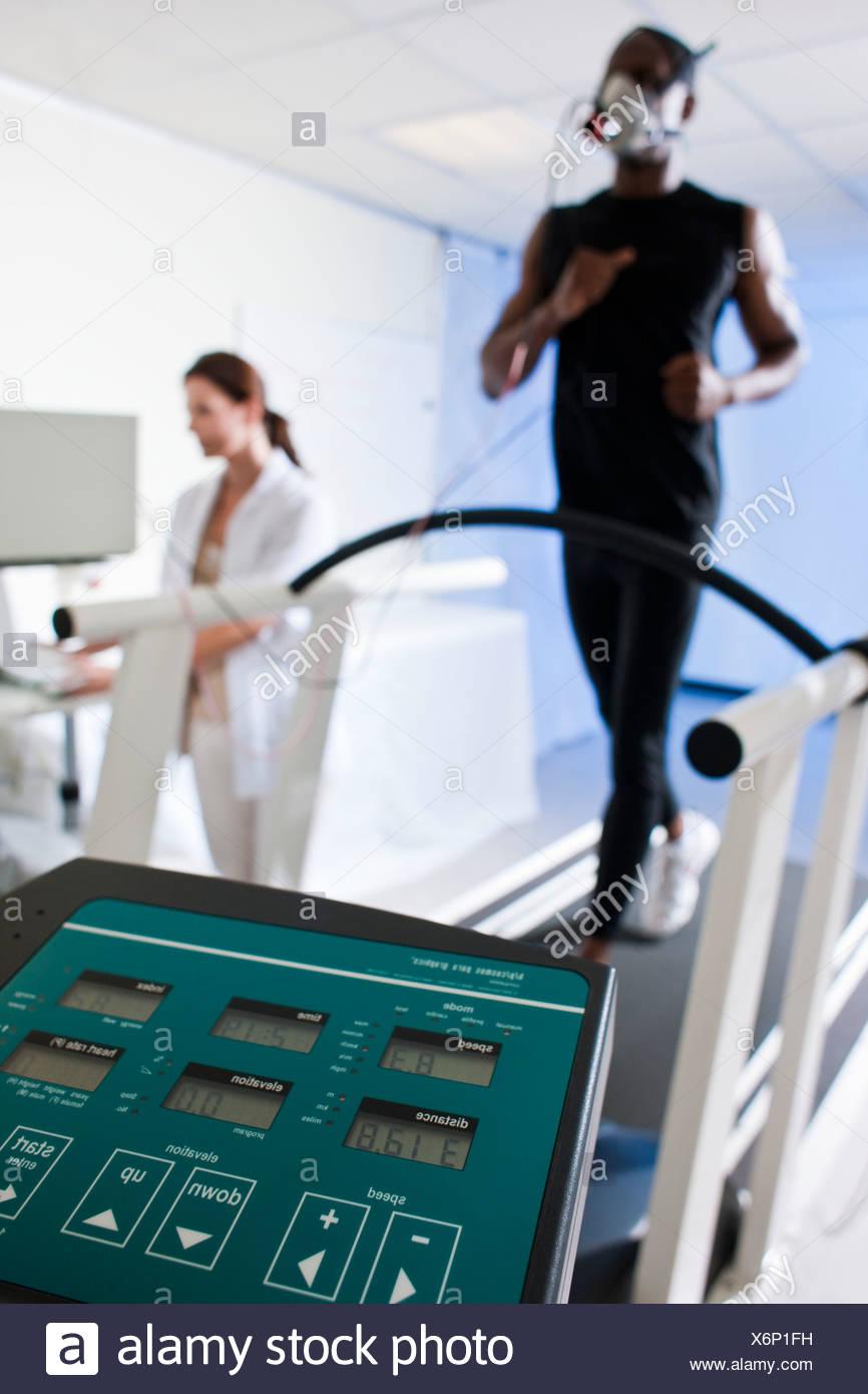 Pruebas de rendimiento liberados modelo atleta corriendo en una cinta andadora su rendimiento y el consumo de oxígeno se miden Imagen De Stock